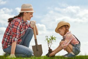 A Mother and Daughter Planting a Tree